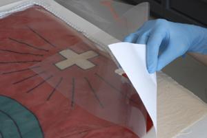 Befeuchten und Glätten einer Fahne. Foto: Schweizerisches Nationalmuseum