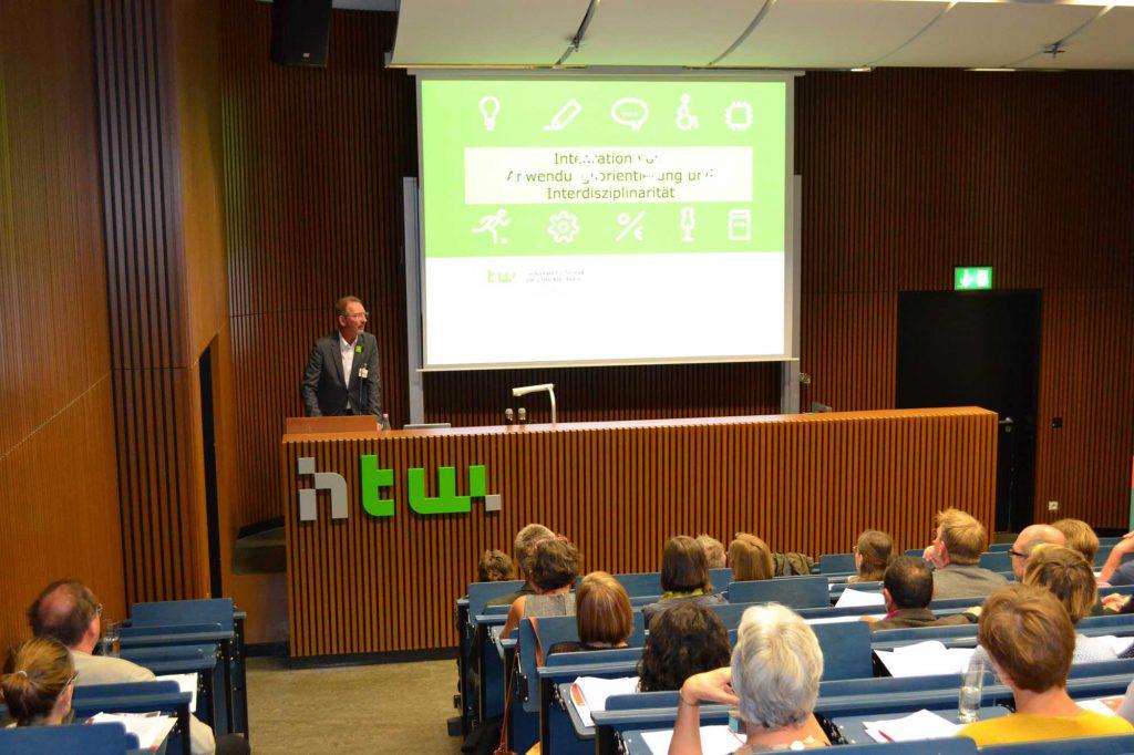 Grußworte der HTW spricht Prof. Dr. Matthias Knaut und betont dabei, wie wichtig es ist, dass kleine Wissenschaftsgebiete mit anderen zusammenarbeiten, um die Wahrnehmung für den Erhalt des Kulturguts zu steigern.
