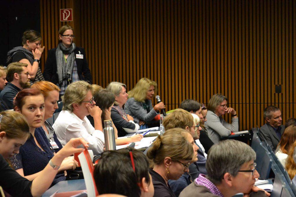 Prof. Dr. Schädler-Saub (hier am Mikrophon) schließt an den Vortrag von Frau Dr. Feldtkeller an. Sie stellt auf der Bühne Theorie und Praxis der wissenschaftlichen Restaurierung in der Baudenkmalpflege vom frühen 20. Jh. bis heute dar.