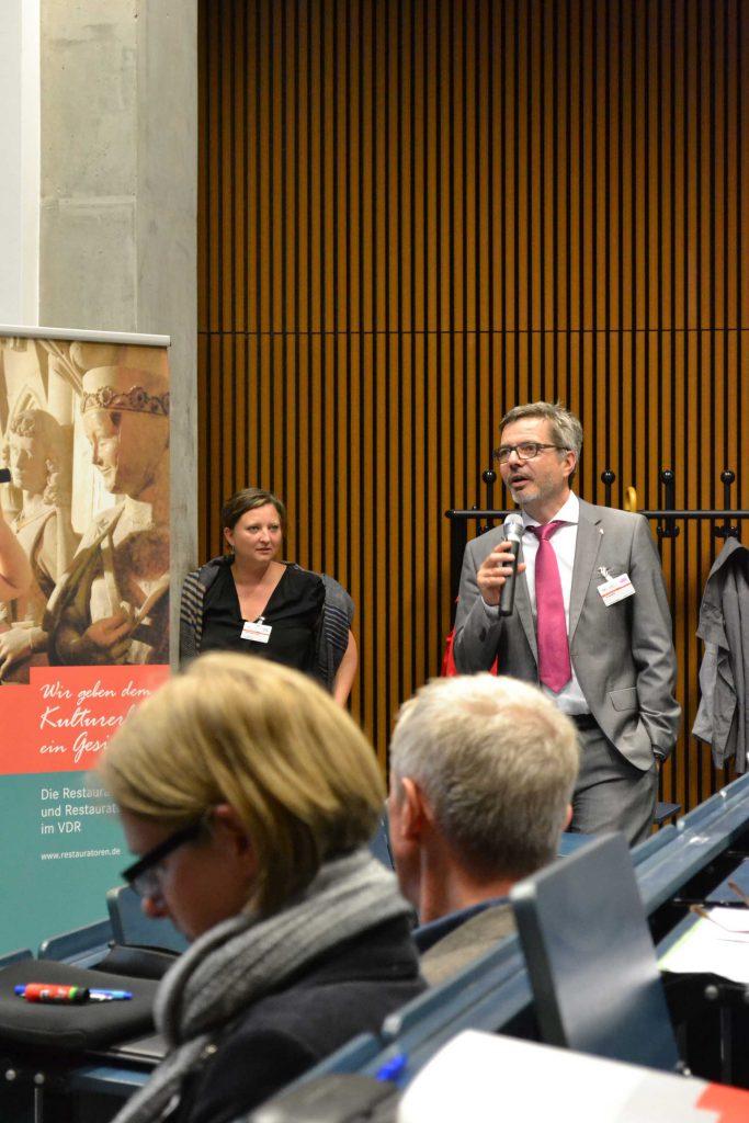 Dr. Jan Raue hat Rückfragen und  lädt das Publikum zu Diskussionen ein.