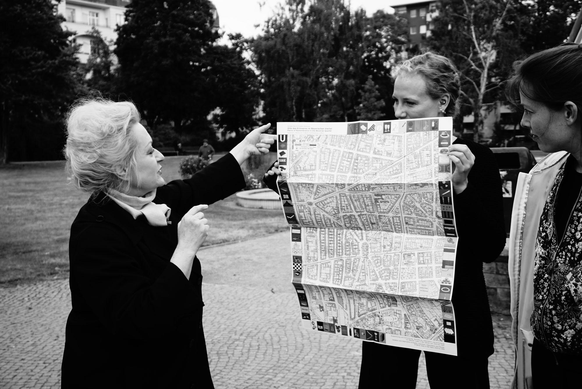 """Abb. 2: Renata Stih erklärt den Teilnehmer*innen die Grundrisskarte. Die Stadtpläne von 1933 und           1993 wurden von Stih und Schnock für ihre Arbeit """"Places of Remembrance/Orte des Erinnerns"""" übereinander gelagert. Foto: Eva Rieß"""