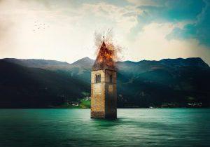 Schnelle Hilfe bei Hochwasser, Bränden und anderen Katastrophen ist das Anliegen des Arbeitsausschusses Kulturgüterschutz im VDR. Foto: Kirchturm im Reschensee, Italien. Fotomontage mit Feuer: Openpics, Pixabay